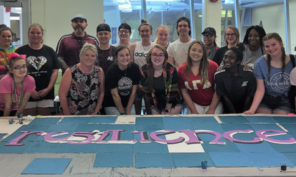 first-year students posing with their work in the Noel Studio discovery classroo