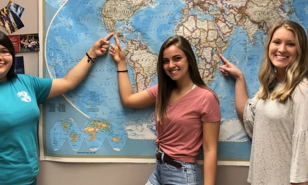 Three Gilman Scholars point to their destinations on a map.