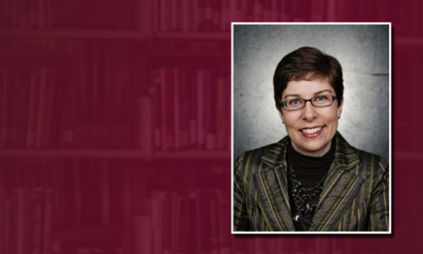 Professional shot of Jackie Jay against a maroon background with library shelf