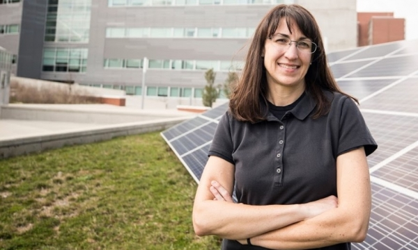 Judy Jenkins standing in front of the New Science Building with a solar panel