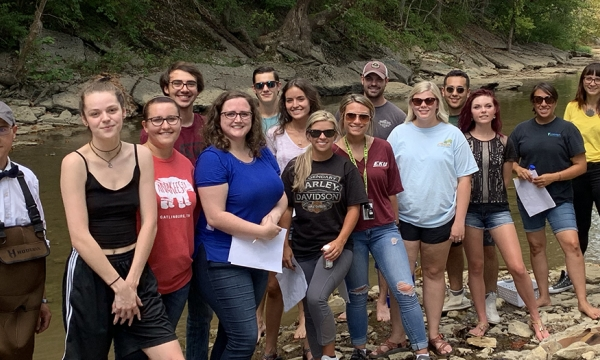 Dr. Jason Marion at a creek with a group of student researchers