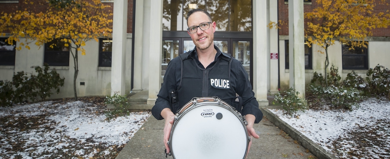 Adam Argullin in front of the Foster Building in a police jacket with his drum
