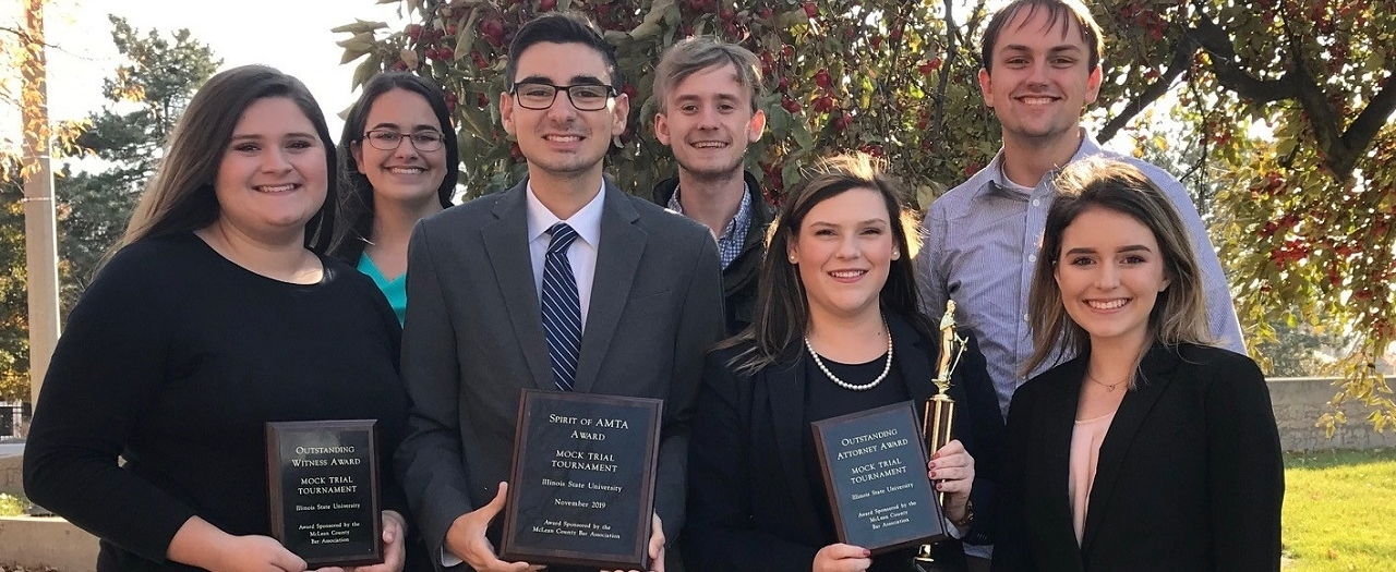 EKU's Mock Trial team holding award plaques and a trophy.