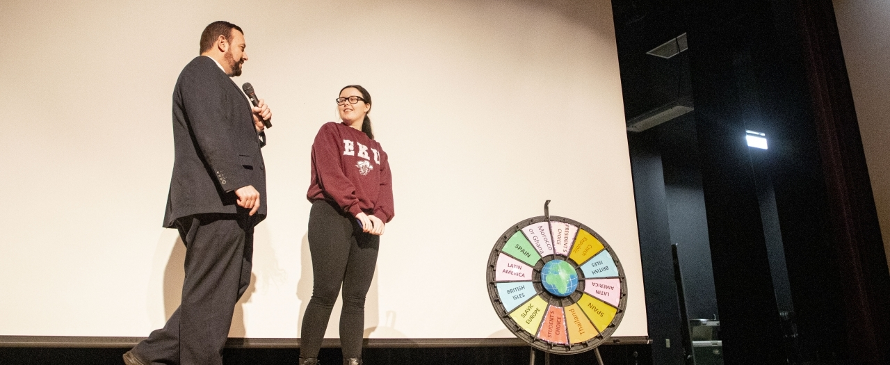 Interim President David McFaddin with a female student about to spin the wheel.