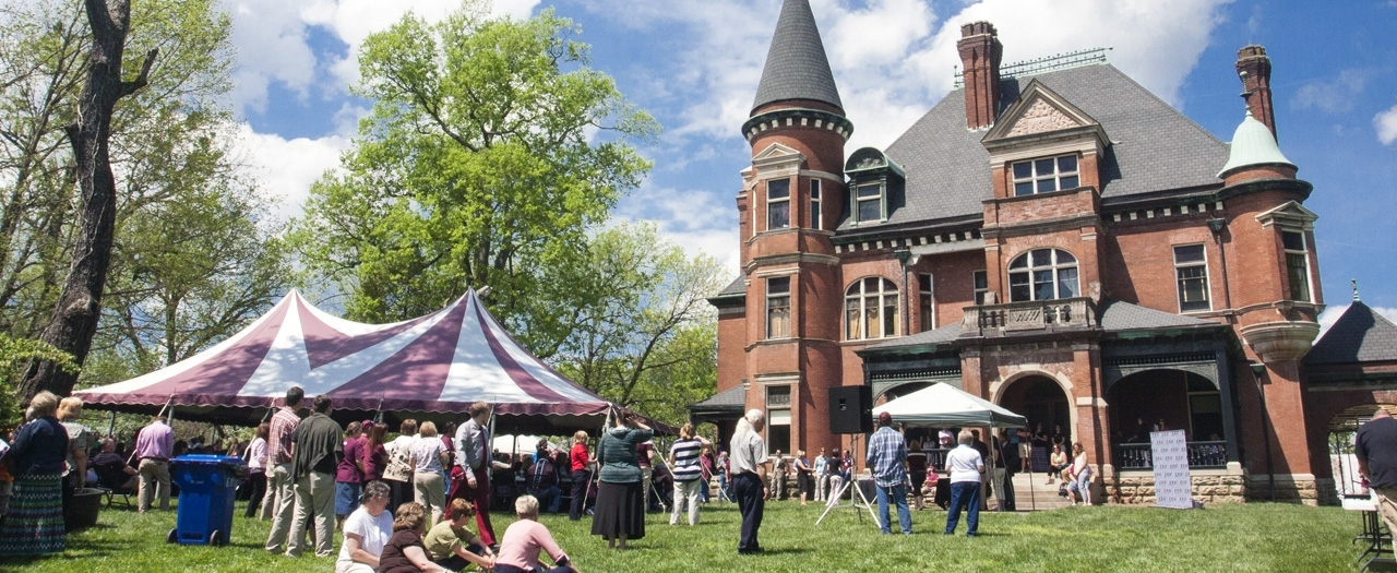 historic Elmwood Estate with tents on the lawn and people standing and sitting