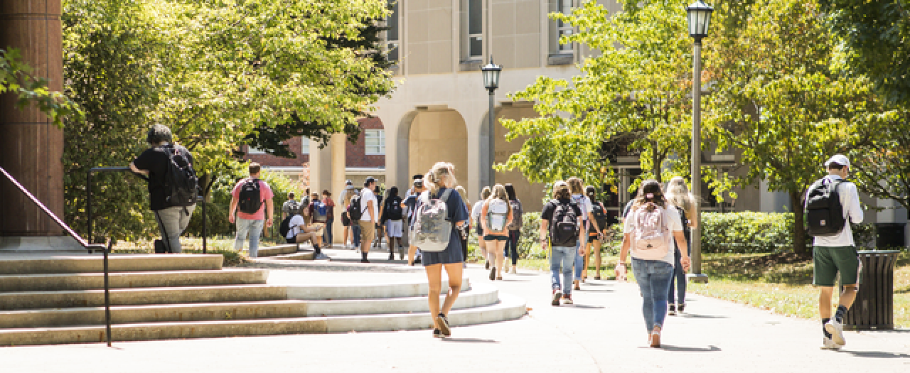 Students walking on Campus, in front of Combs Building and beside Crabbe Library