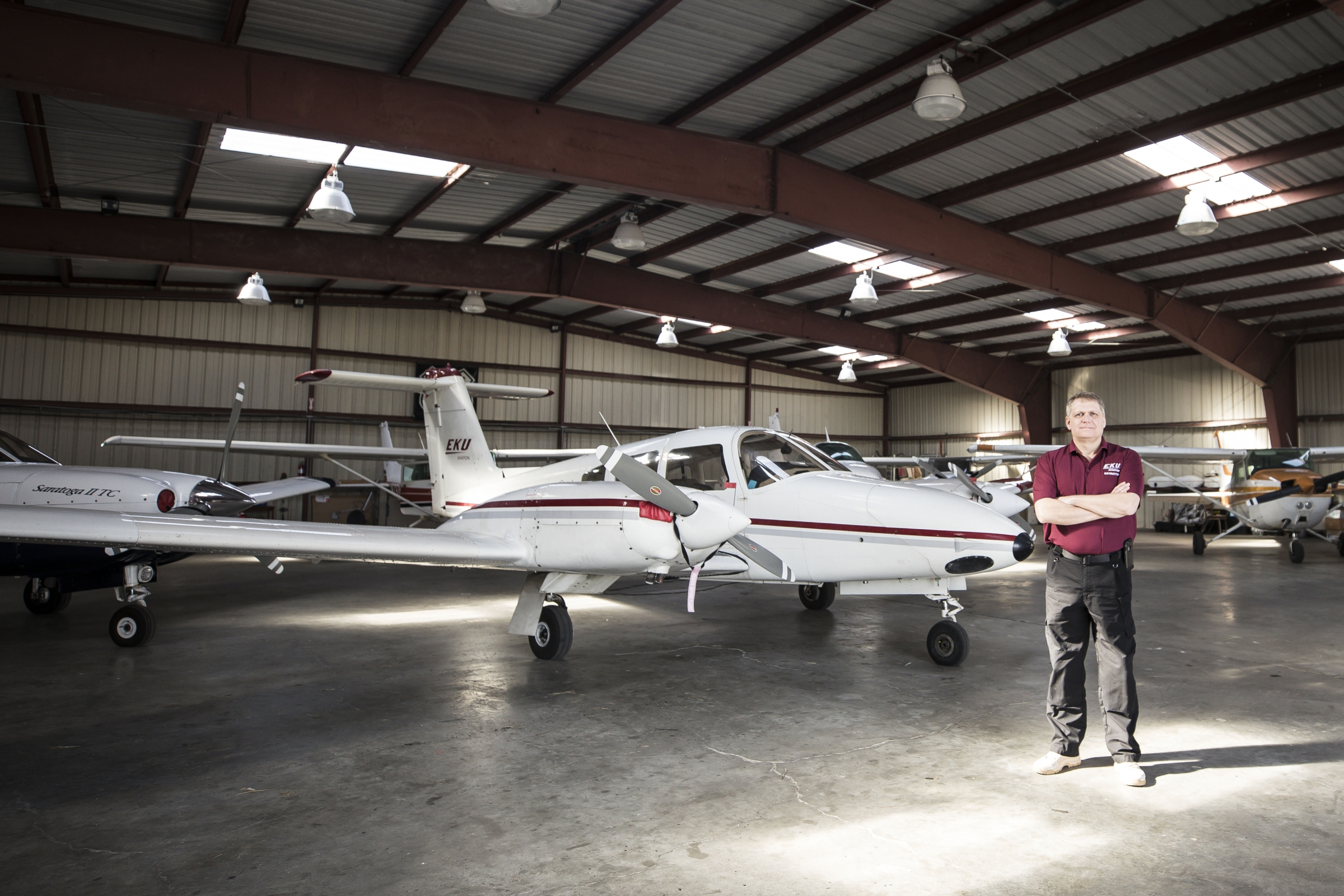 Sean Howard stands in front of an airplane in hanger.